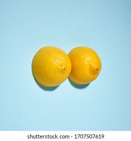 Two yellow lemons on a bright blue background, imitation of a beautiful female breast.