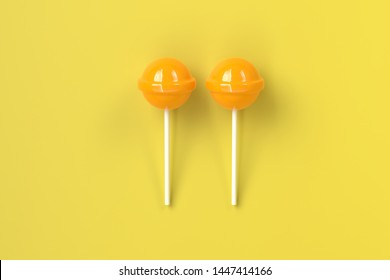 two yellow lolipop on yellow pastel background.sweet candy concept