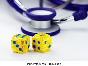 Two yellow marbled yellow dice with blue dots for numbers in front of a purple stethoscope, asking the question do you gamble with your health?