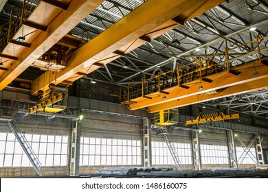 Two yellow overhead cranes in engineering plant shop. Industrial metalwork production hall and warehousing workshop.