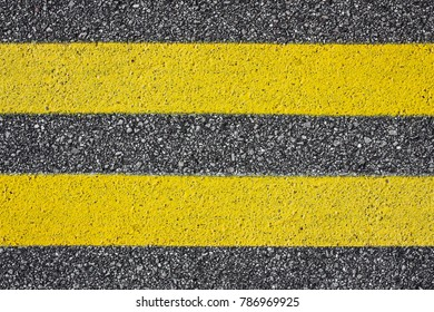 Two yellow paint asphalt lines. Copy space transportation safety background.