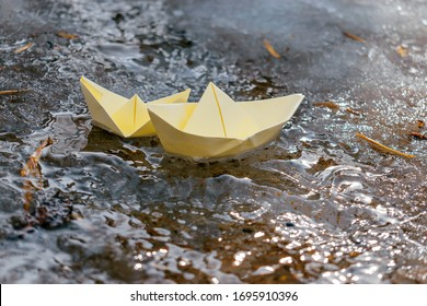 Two yellow paper boats sail along the stream. Spring concept.Concept of travel during coronavirus quarantine.Selective focus.