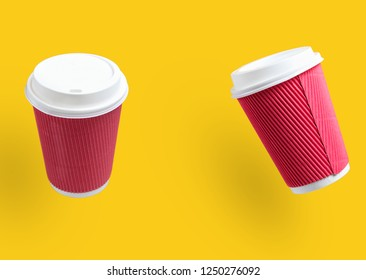 Two yellow paper coffee cups on yellow background. Minimalism. Copy space.