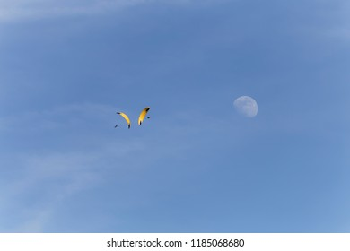 Two yellow parapenters dancing around each other by the moon above Lake Annecy France