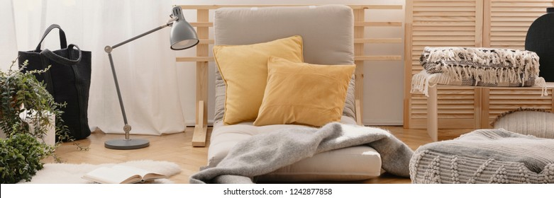 Two yellow pillows placed on futon mattress chair in real photo of bright living room interior with metal lamp, fresh plants, natural materials and book on the floor
