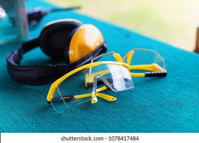two yellow protective glasses eyes and protective ears on table in shooting range.
