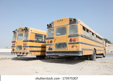 Two yellow school buses in a parking lot. Doha, Qatar, Middle East