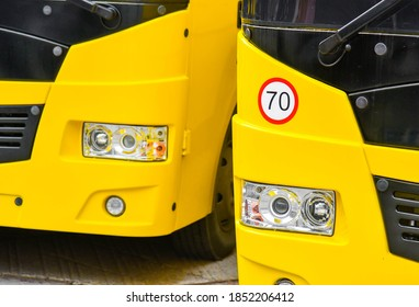 Two yellow school buses and a speed limit sign (70 kilometers)