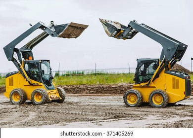 two yellow skid steers with raiced bucket outdoors
