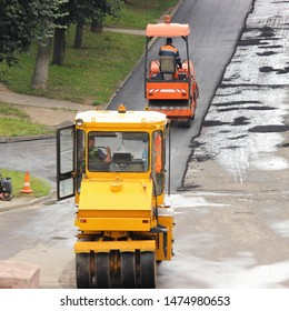 Two yellow steamrollers laying of asphalt in city Park, industrial machinery - asphalt roller on summer day, renovation of the road, worker people