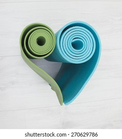 two yoga mats stacked in the shape of heart green and blue colors
