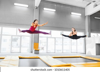 Two young active women jumping on trampolines in a modern fitness center