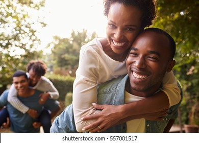 Two young adult black couples piggybacking look to camera