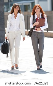 two young adult caucasian businesswoman walking outdoors watching in camera