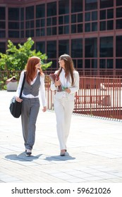 two young adult caucasian businesswoman walking outdoors while talking