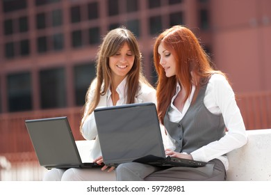 two young adult caucasian businesswoman,working outdoors with two laptop