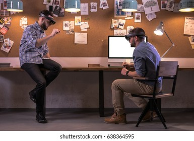 Two young adult Caucasian males discussing a project using holographic augmented reality glasses in trendy office. Future business concept