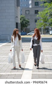 two young adult caucasian woman walking while carrying shopping bags
