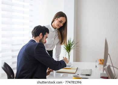 Two young adult colleagues working at the office