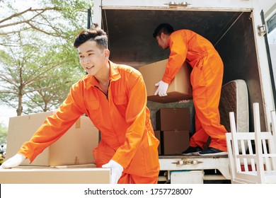 Two young adult men wearing orange uniform clothes loading truck with household things