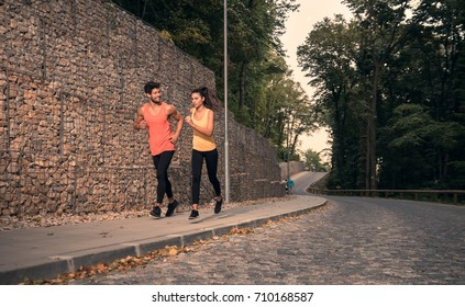 two young adult people, jogging, outdoors nature forest asphalt, sport clothes, happy smiling