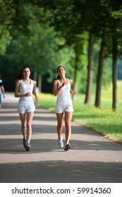 two young adult woman running in a park