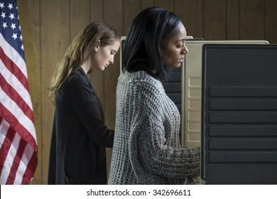 Zwei junge erwachsene Frauen, die an einem Wahlstand teilnehmen