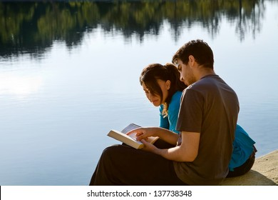 Two young adults sitting by a lake and studying the Bible (King James Version)