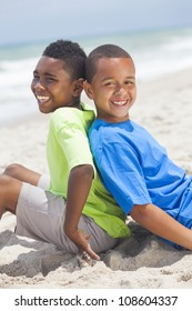 Two young African American boys sitting back to back playing having fun on a sunny beach