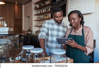 Two young African entrepreneurs working together on a digital tablet at the checkout counter of their trendy cafe