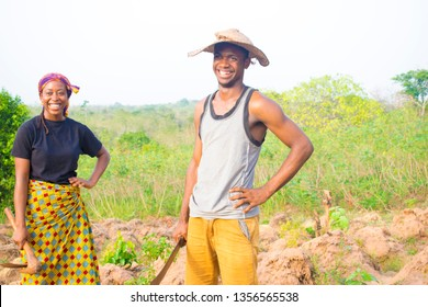two young African farmers holding hoe and cutlass smiling at camera