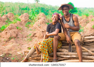 two young African farmers sitting on a pile of wood on a farm laughing together