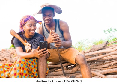 Two Young African Farmers using their mobile phone
