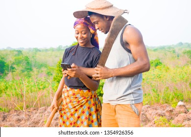two young African farmers using their mobile phone checking emails, shopping online