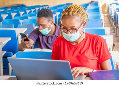 two young african students in a classroom, one using a laptop, both wearing face masks