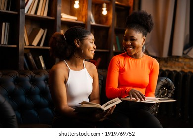 two young african women reading books in the library