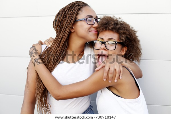 Two young afro girls having fun together, joy, positive, love, friendship, sisters. Happy meeting of two friends hugging in the street