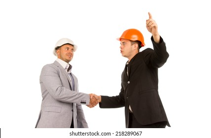 Two Young Angry Male Engineers in Gray and Black Coats Shaking Hands on White Background.