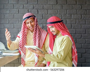 Two young arab businessmen discuss business through tablet at meeting in cafe