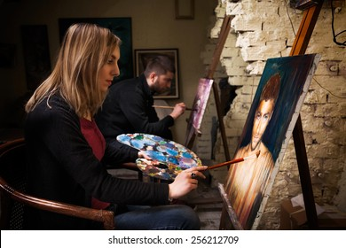 Two young artists working on oil paintings in art studio.