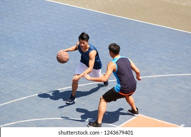 two young asian basketball players playing one on one on outdoor court.