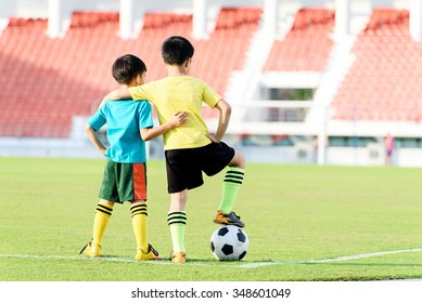 Two Young Asian boy stand in the grass football field in the stadium during summer.