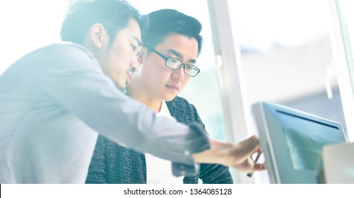 two young asian corporate executives working together using desktop computer.