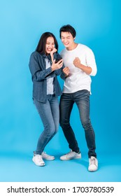 Two of young Asian couple man and woman using mobile phone with happy and cheerful surprise over blue background, studio shot full length