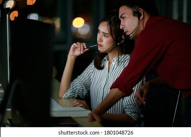 Two young Asian customer services operators discuss and working night shift in call center for helping assistance client in workplace at night time. Night shift Call center business operator concept