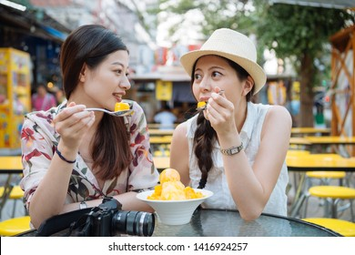 Two young asian female friends travelers having fun and eating ice cream. Cheerful women tourists eating mango shaved ice in summer hot outdoors using spoon sit in local cafe shop. cool fresh fruit