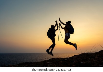Two young Asian female  hiking jumping in the mountain holiday, wild adventure. Background for Travel concept. sunset silhouette.