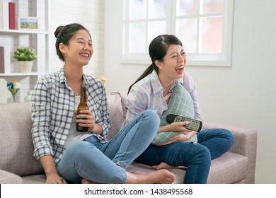 two young asian female people having day off relaxing in front of tv in cozy living room. girl friends spending weekend together sitting on sofa laughing over extremely amusing tv-show drinking beer.