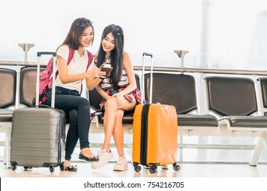 Two young Asian girl using smartphone check flight or web check-in, sit at airport waiting seat together. Air travel lifestyle, exciting summer vacation trip or mobile phone gadget application concept