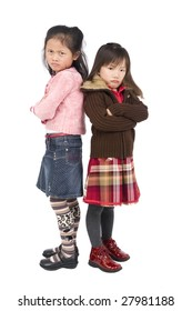 Two young asian girls pouting over something